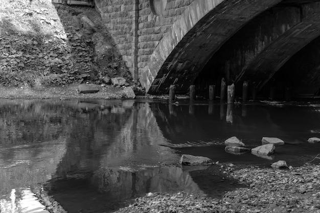 Kleiner stadtfluss mit einem fragment einer alten bogenbrücke, monochromes foto