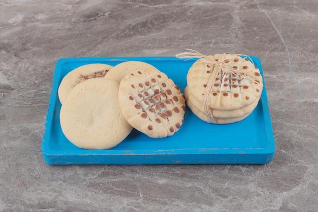 Kleiner stapel kekse auf einer blauen platte auf marmor