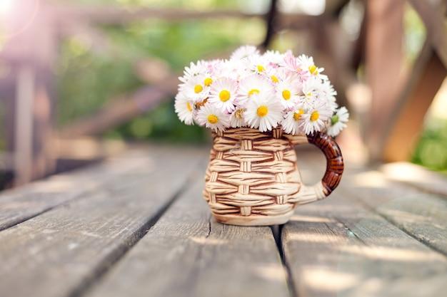 Kleiner strauß gänseblümchen in der tasse auf grunge-holzbrett vor grünem hintergrund kleines blumengeschenk muttertag daisy bellis perennis gartenblumen