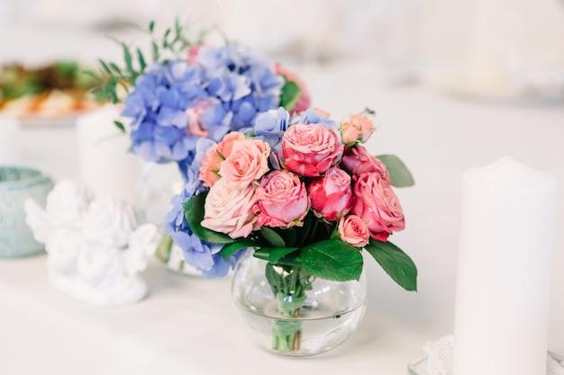Kleiner strauß rosa rosen in glasvase