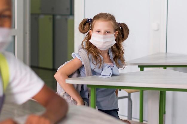 Kleiner student, der eine medizinische maske trägt