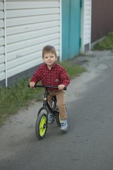 Kleiner süßer junge auf dem fahrrad am sommer- oder herbsttag. gesundes glückliches kind, das spaß mit dem radfahren auf dem fahrrad hat.