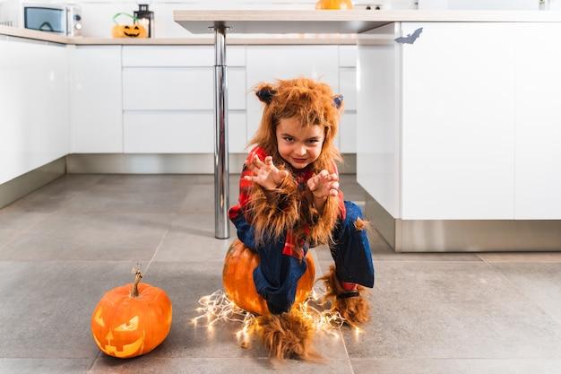 Kleiner süßer junge, der als werwolf verkleidet ist und gestikuliert, während er die kamera während der halloween-feier erschreckt