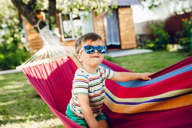 Kleiner süßer junge, der auf heller hängematte sitzt und spaß hat.