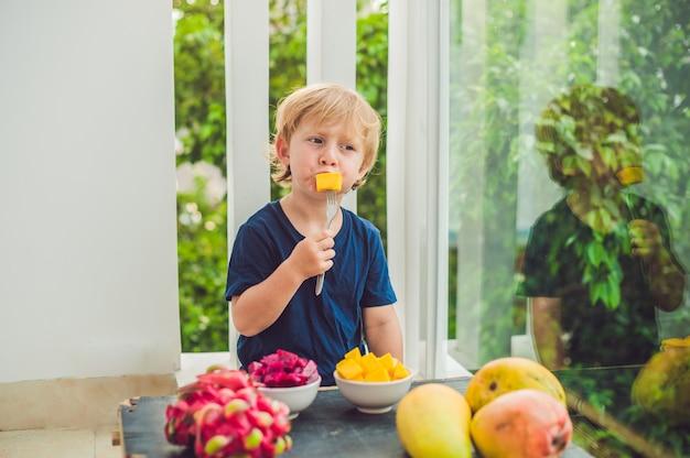 Kleiner süßer junge, der mango auf der terrasse isst