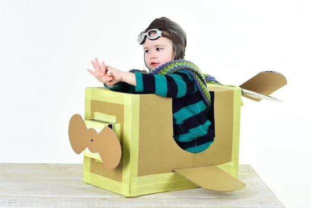 Kleiner süßer junge, der mit einem pappflugzeug spielt. karton im retro-stil