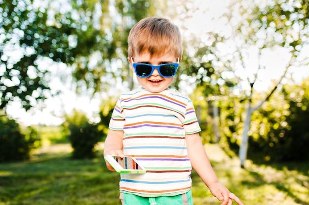 Kleiner süßer junge, der telefon in seiner hand hält und im sommergarten lächelt.