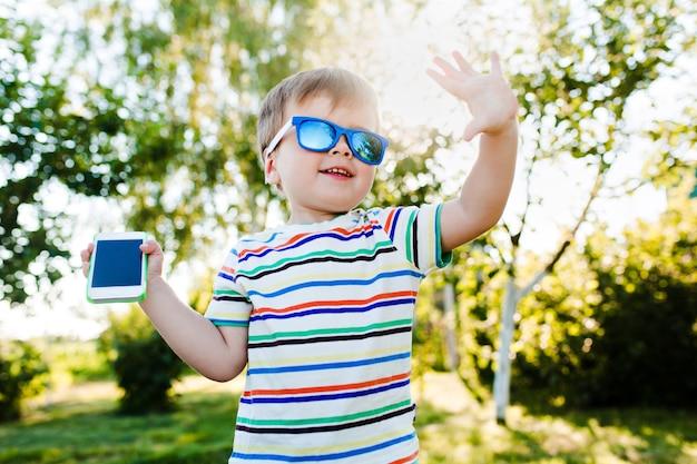Kleiner süßer junge gibt eine hohe fünf und hält ein telefon in der hand.