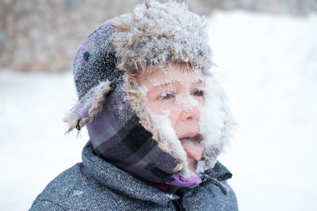 Kleiner süßer junge im winterhut mit schneebedecktem gesicht. seitenansicht.