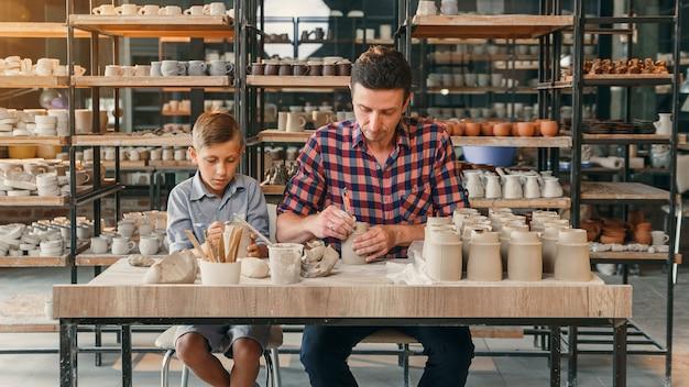 Kleiner süßer junge mit seinem vater, der keramiktöpfe in der keramik macht.