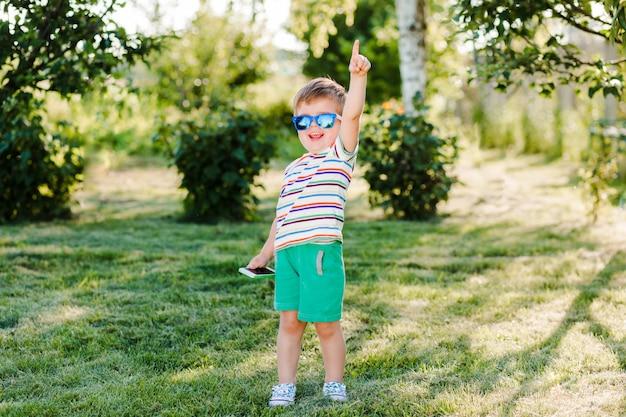 Kleiner süßer junge sieht inspiriert und glücklich in der hellen sonnenbrille mit seinem telefon aus.