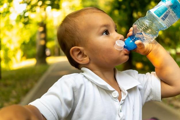 Kleiner süßer junge trinkt wasser im park und plastikflasche an heißen sommertagen müde von der durstfamilie