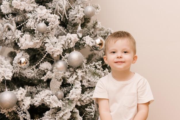 Kleiner süßer kleiner junge, der im kinderzimmer neben dem weihnachtsschneebaum sitzt