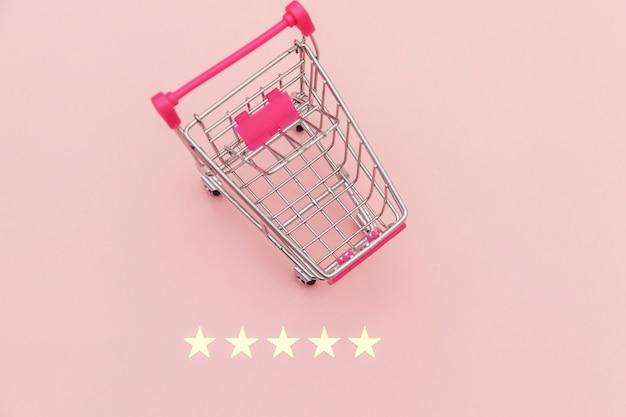 Kleiner supermarkt-lebensmittel-schubkarren für einkaufsspielzeug mit rädern und 5-sterne-bewertung isoliert auf pastellrosa. einzelhandelskunden kaufen online-bewertungs- und überprüfungskonzept.