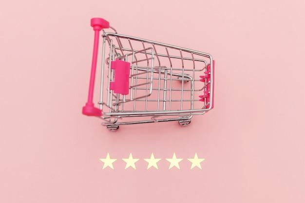 Kleiner supermarkt lebensmittelgeschäft push cart für einkaufsspielzeug mit rädern und 5 sterne bewertung isoliert auf pastellrosa hintergrund. einzelhandelskunden kaufen online-bewertungs- und überprüfungskonzept.