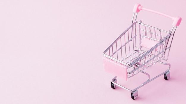 Kleiner supermarktlebensmittel-schubkarren für einkaufsspielzeug mit rädern und rosa plastikelementen auf rosa pastellfarbenem papier flach legen hintergrund. konzept des einkaufens. kopieren sie platz für werbung.