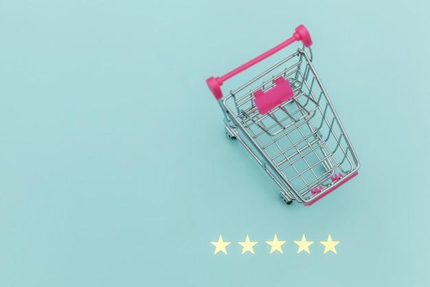 Kleiner supermarktlebensmittel-schubwagen für einkaufsspielzeug mit rädern und 5-sterne-bewertung isoliert auf pastellblauem hintergrund. einzelhandelskunden kaufen online-bewertungs- und überprüfungskonzept.