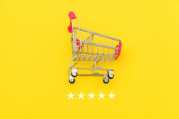Kleiner supermarktlebensmittel-schubwagen für einkaufsspielzeug mit rädern und 5-sterne-bewertung lokalisiert auf gelbem hintergrund.