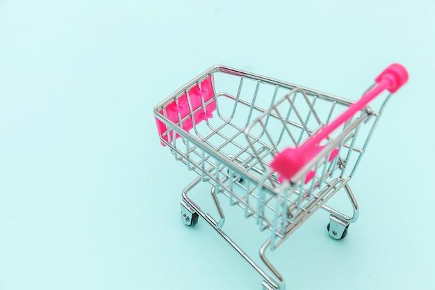 Kleiner supermarktlebensmittelgeschäft-stoßwarenkorb für das einkaufsspielzeug mit den rädern lokalisiert auf blauem buntem modischem hintergrund kopienpastellraum. verkaufskaufmall-marktshop-verbraucherkonzept.