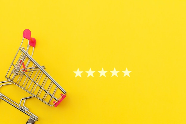 Kleiner supermarktlebensmittelgeschäft-stoßwarenkorb für das einkaufsspielzeug mit rädern und bewertung mit 5 sternen lokalisiert auf gelbem hintergrund. einzelhandelsverbraucher kaufen online-bewertung und review-konzept.