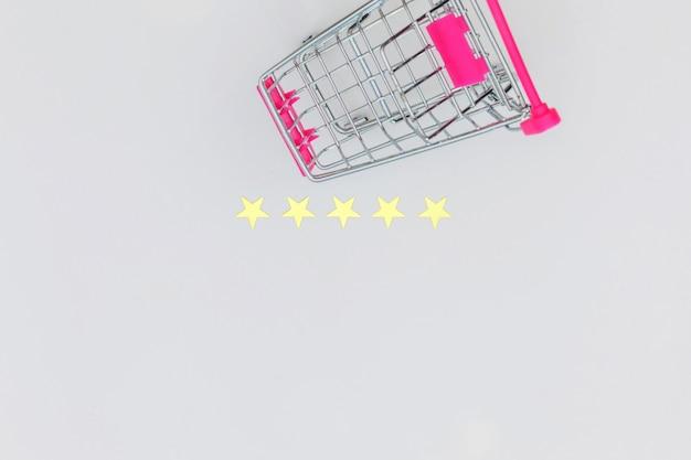 Kleiner supermarktlebensmittelgeschäft-stoßwarenkorb für das einkaufsspielzeug mit rädern und bewertung mit 5 sternen lokalisiert auf weißem hintergrund. einzelhandelsverbraucher kaufen online-bewertung und review-konzept.