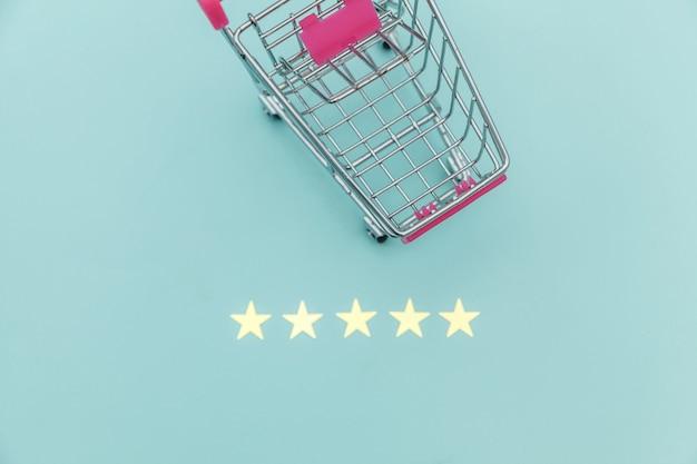 Kleiner supermarktlebensmittelgeschäft-stoßwarenkorb für einkaufsspielzeug mit rädern und der bewertung mit 5 sternen lokalisiert auf blauem pastellhintergrund. einzelhandelsverbraucher kaufen online-bewertung und review-konzept.