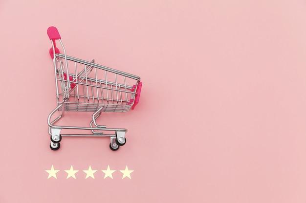 Kleiner supermarktlebensmittelgeschäft-stoßwarenkorb für einkaufsspielzeug mit rädern und der bewertung mit 5 sternen lokalisiert auf pastellrosahintergrund. einzelhandelsverbraucher kaufen online-bewertung und review-konzept.