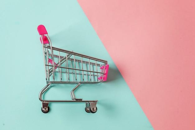 Kleiner supermarktlebensmittelgeschäftspielzeug-stoßwarenkorb auf blauem und rosa hintergrund