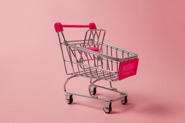 Kleiner supermarktlebensmittelgeschäftspielzeug-stoßwarenkorb auf rosa hintergrund