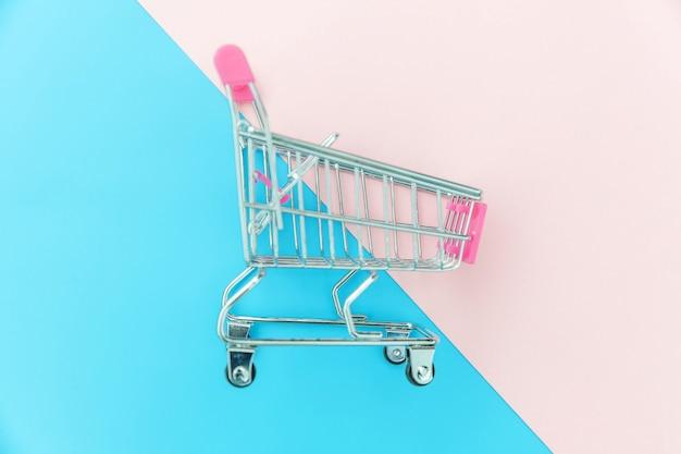 Kleiner supermarktlebensmittelgeschäftspielzeug-stoßwarenkorb lokalisiert auf blauem und rosa buntem pastellhintergrund