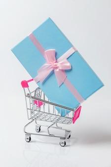 Kleiner supermarktlebensmittelgeschäftspielzeugstoßwarenkorb und geschenkbox auf weißem hintergrund
