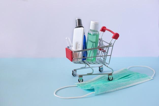 Kleiner supermarktwagen mit alkoholgel, antibakteriellem handspray und coronavirus-prüfstand auf medizinischer maske. pandemisches gesundheitskonzept