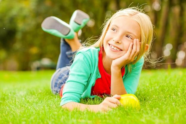 Kleiner tagträumer. nettes kleines mädchen, das den kopf zur hand lehnt und mit einem lächeln wegschaut, während es auf dem grünen gras liegt
