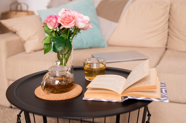 Kleiner tisch mit rosenstrauß in glas wasser, grünem tee in teekanne und tasse und offenem buch der geschichten gegen couch mit kissen und tablette
