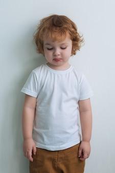 Kleiner trauriger junge im weißen t-shirt
