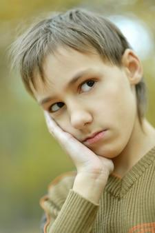 Kleiner trauriger junge in einem warmen pullover für einen spaziergang im herbst