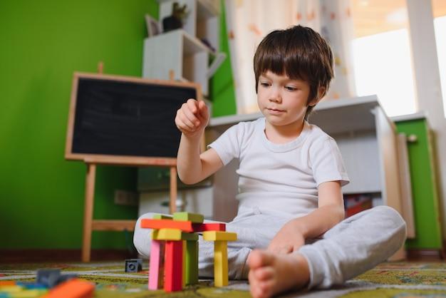 Kleiner trauriger nachdenklich gelangweilter kleinkindjunge, der allein zu hause während der quarantäne bunte bausteine spielt