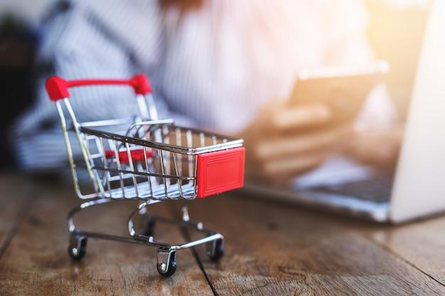 Kleiner trolley mit jungen frauen nutzen smartphone und laptop.