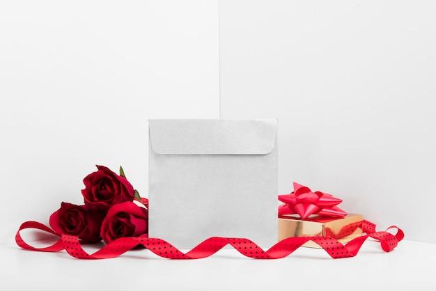 Kleiner umschlag mit geschenkbox auf dem tisch