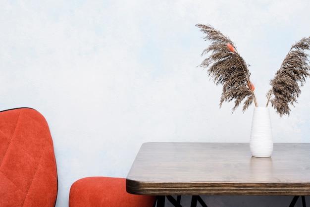 Kleiner vase der nahaufnahme mit getrockneten anlagen