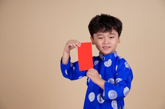 Kleiner vietnamesischer junge, der rote umschläge für tet hält.