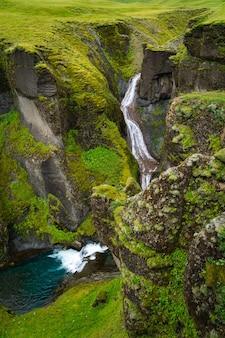 Kleiner wasserfall, der in einen moosigen canyon in island einspeist