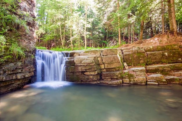 Kleiner wasserfall im bergwald mit seidigem schaumwasser