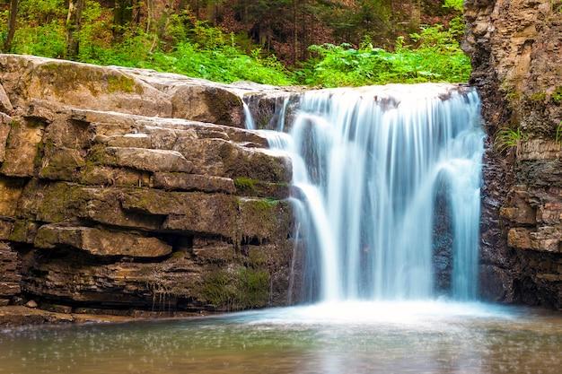 Kleiner wasserfall im gebirgswald mit seidigem schäumendem wasser