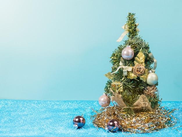 Kleiner weihnachtsbaum auf einer blauen oberfläche