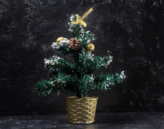 Kleiner weihnachtsbaum auf schwarzem abstraktem hintergrund.