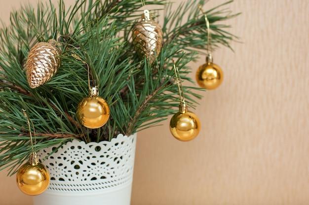 Kleiner weihnachtsbaum in einem weißen eimer verziert mit weihnachtskugeln auf dem tisch