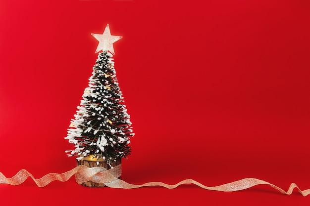 Kleiner weihnachtsbaum mit band auf rotem grund. foto in hoher qualität