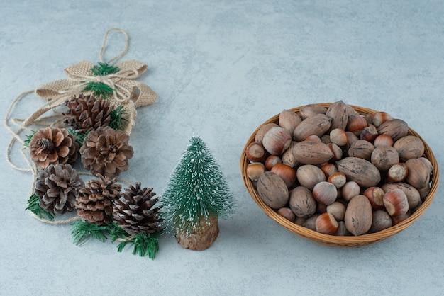 Kleiner weihnachtsbaum mit korb der nüsse auf marmorhintergrund. hochwertiges foto