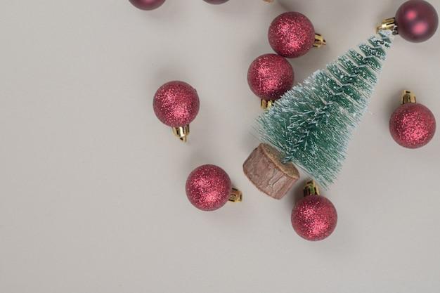 Kleiner weihnachtsbaum mit roten weihnachtskugeln auf weißer oberfläche